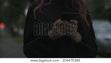 female teen using smartphone on the street at night, wide photo