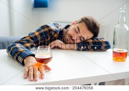 Alcohol drunkard man is drinking himself to sleep