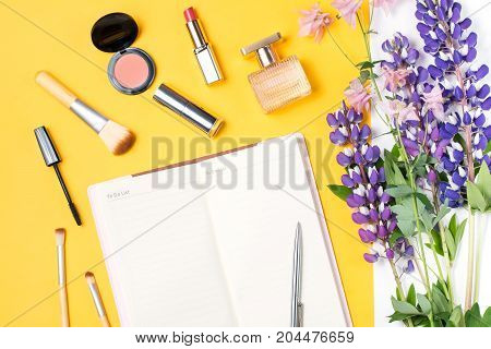 Modern woman accessories. Beauty products, note book, accessories, flowers on a pastel background. Feminine composition
