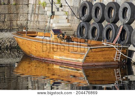 Reflection in the water of a wooden motor boat moored on the quay