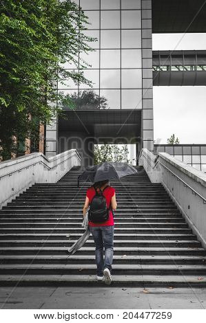 young woman walking alone climb the stairs in a modern neighborhood of a big city while holding an umbrella under rain