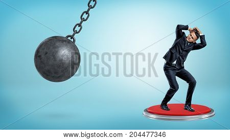 A scared cowering businessman stands on a huge push button and hides his head from a wrecking ball. Business results. Decision making. Responsibility.