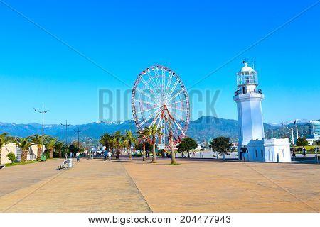 Batumi, Georgia - April 30, 2017: Ferris wheel, city panoramic landscape with palm trees and mountain peaks of Batumi, Georgia summer Black sea resort