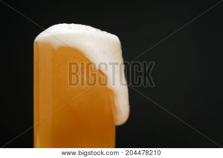 wheat unfiltered beer poured into glass over dark background, with copy space