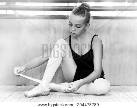 Young ballerina in the hall for rehearsals. Black and white photo. Ballet. Creation. Dancing.