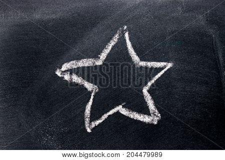 White chalk hand drawing as star shape on black board background