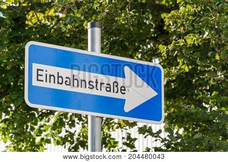 German One Way Street Sign With Trees In The Background
