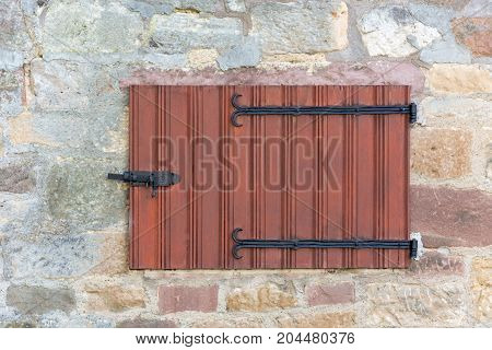 Old Wooden Medieval Window Shutters On A Stone Wall