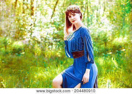 woman in a dress in a wood near a tree