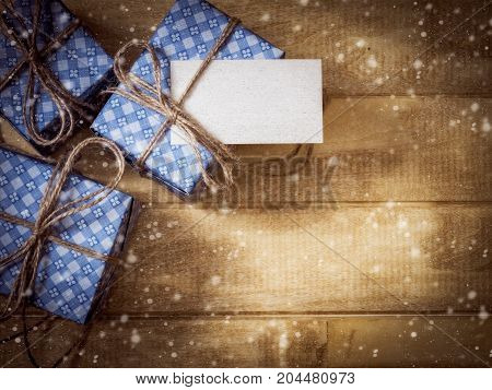 Top view of gift box in blue paper decorated with linen cord and sticker with place for customer's note on the wooden table. Drawn snow. Dark toned