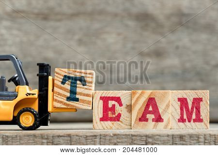 Yellow plastic forklift hold letter T to complete word TEAM on wood background