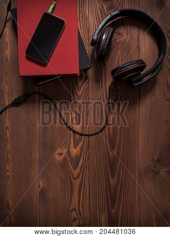 Concept of audiobook. Books on the table with cellular phone headphones next to them. Top view