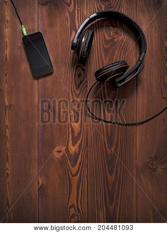 Earphones and mobile smartphone lying on the table. Top view