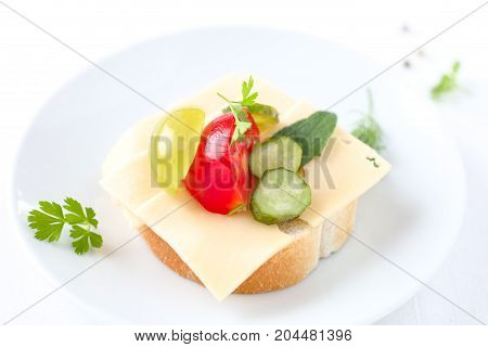Sandwich with slices of cheese, tomato, cucumber and grape.