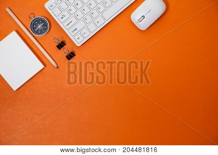 Office desk table of Business workplace and business objects of keyboardmousewhite papernotebookpencilcompass on orange background