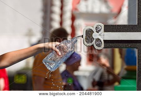 A woman hand pouring the holy water in a bottle from the Holy spring at the Sergiyev Posad monastery. Moscow region, Russia.
