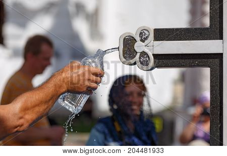 A man pouring the holy water in a bottle from the Holy spring at the Sergiyev Posad monastery. Moscow region, Russia.