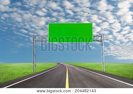Blank billboard for your advertisement with space for text on road curvewith green grass and blue sky white cloud