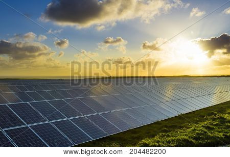 Solar Panels At Sunrise With Cloudy Sky And Sunbeams In Normandy, France. Solar Energy, Technology O