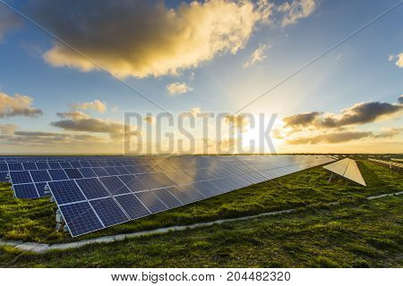 Solar Panels At Sunrise With Dramatic Cloudy Sky In Normandy, France. Modern Electric Power Producti