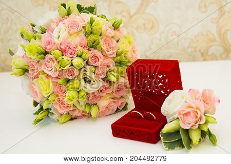 Gold Wedding Ring, Red Box, Groom's Boutonniere And A Bouquet Of Flowers Bride