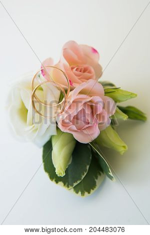 Groom's Boutonniere With A Pink Rose And Two Wedding Gold Rings