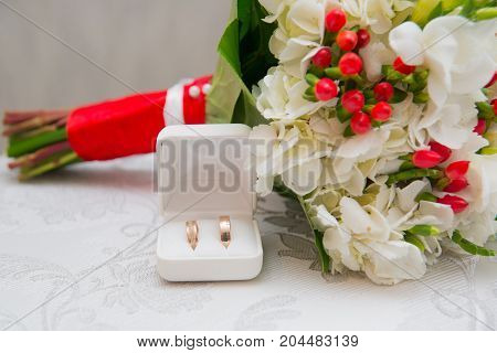 Two Golden Wedding Rings In White Box And Bouquet With White Flowers And Red Berries.