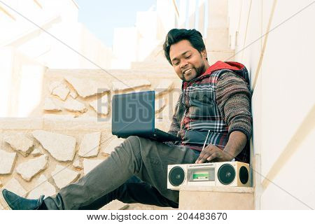 Young indian man using laptop listening at music radio outdoors - Asian student with pc turning cassette player on sitting outside urban building on spring day - Old and new technology concept