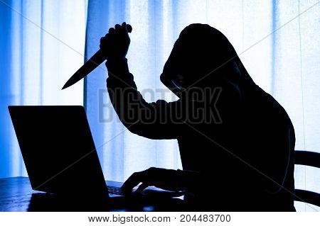 Hooded dark man at pc brandishing knife with a threatening attitude - Dangerous cyber stalker holding sharp blade at laptop in the darkness - Concept of internet harassment with focus on evil face