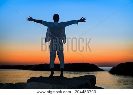 Silhouette of young man raising arms at sunset standing by the sea - Male person contemplating the dusk in winning attitudes rising on the rocks on seascape background - Twilight with enhanced tones