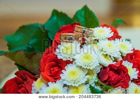 Two Gold Wedding Rings Lie On A Bouquet With White Flowers And Red Roses.