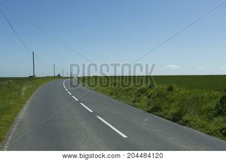Asphalt Empty Road Passing Through The Fields In The Region Of Normandy, France. Landscape In Spring