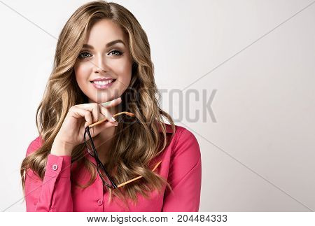 Young businesswoman holding glasses in hand and smiles genuinely welcoming customer. Beautiful girl holding glasses in her hands and looks at you  with a sincerely smile .