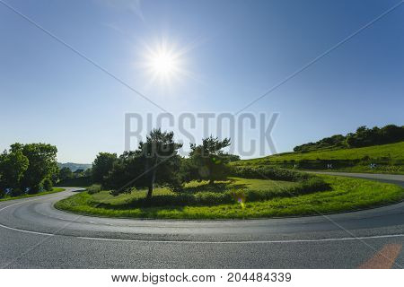 Empty Asphalt Curvy Road Passing Through Green Fields And Forests. Countryside Landscape On A Sunny