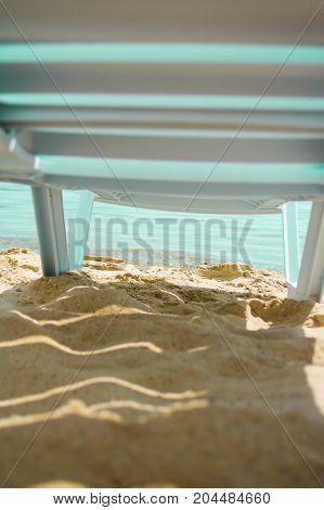 Deck-chair standing on the pier by sea lights sun beach sand