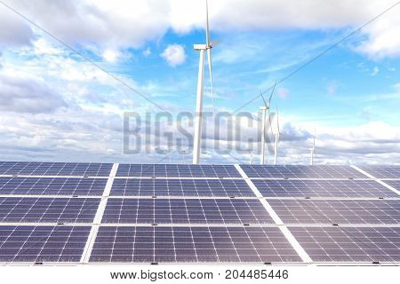 Solar power panels Photovoltaic modules for innovation green energy for life and wind turbines against with blue sky background .