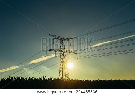 High Voltage Power Lines And Transmission Towers With Sunbeams In The Blue Sky In Normandy, France.