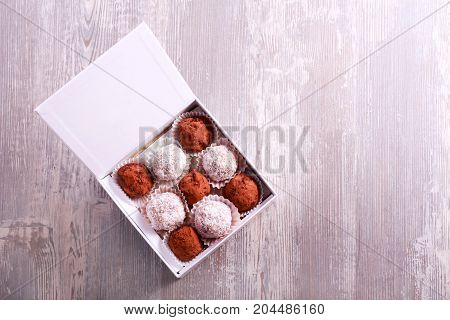 Homemade truffle and fruit candies in a box top view