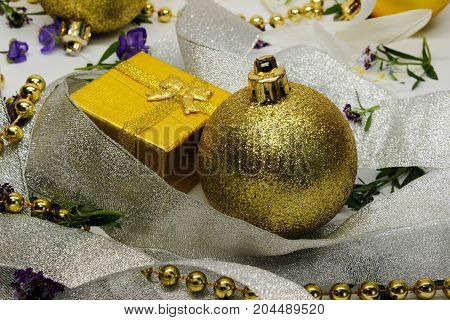 a golden gift box and a Christmas toy shrouded in silver ribbon and small purple flowers