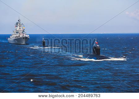 A line of modern russian military submarine cruisers in the row, northern fleet and baltic sea fleet in the open sea, submarine