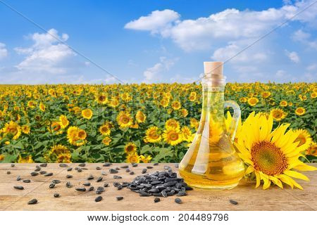sunflower oil in glass bottle, pile of sunflower seeds, fresh sunflowers on wooden table with natural background. Blooming sunflower field with blue sky. Agriculture and harvest concept