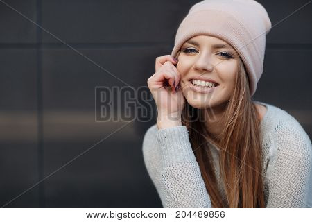 Cute girl with blue eyes,long, straight,light brown hair,beautiful smile ,dressed in a knit pullover, gray-blue color,wearing a sports cap pink,light makeup,spends time alone in the city,posing against the backdrop of the gray wall,spring portrait