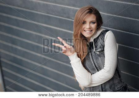 Cute girl with blue eyes,long, straight,light brown hair,beautiful smile,dressed in a knitted pullover blue-gray and gray jacket with no sleeves,minimal makeup,spends time alone in the city,posing against the backdrop of the gray wall,spring portrait