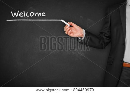 Back to business school. Heading (title) with text welcome written by teacher on chalkboard.