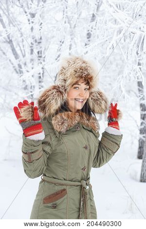 happy young woman outdoors in winter. Closeup portrait of a beautiful smiling girl in fur hat, knitted gloves in winter forest. Beautiful girl in winter clothes. People, winter, rest, outdoors concept