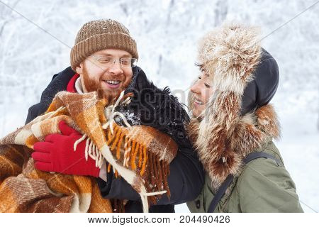 portrait of happy winter couple with pet small dog scottish terrier. Young man and woman in love with dog walking in the snowy forest. Family playing with dog. People, winter, rest, outdoors concept