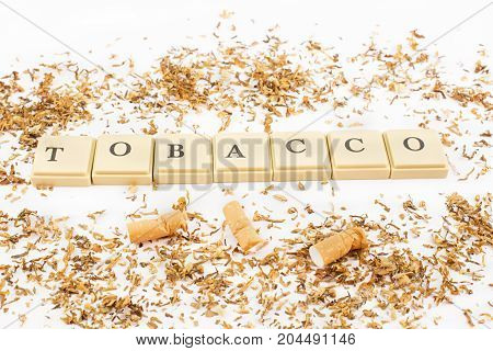 Tobacco written with cigarette chips and cigarette butts. White background.
