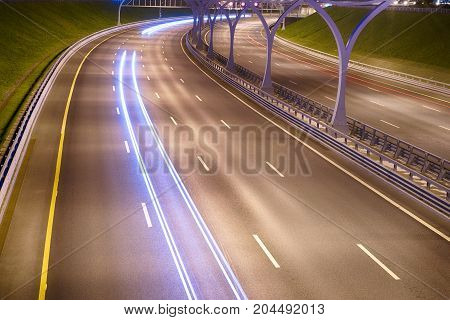 Illuminated highway with traces at night. Long exposure