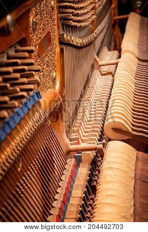 Inside old piano view. Ancient musical mechanism close up