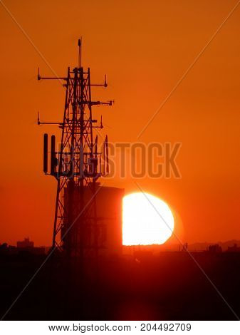The sun setting behind a communication Tower